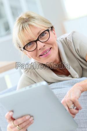 senior woman with eyeglasses using digital