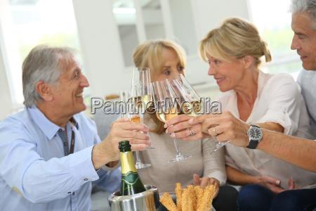 gruppe aeltere menschen feiern mit champagner