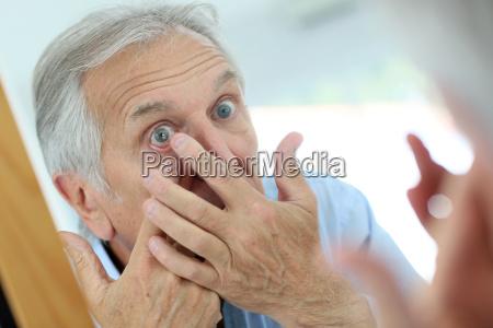 closeup of senior man putting contact