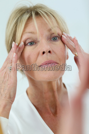 senior woman looking at her skin