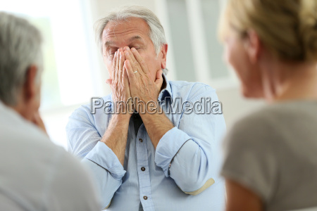 senior man attending meeting with group