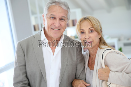 happy retired couple standing in new
