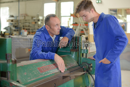 man and apprentice by industrial machine