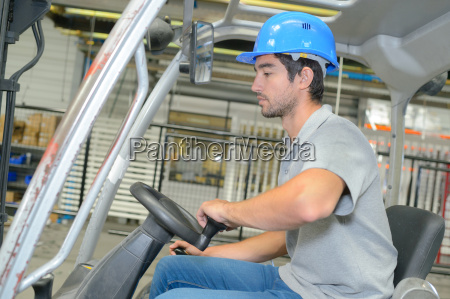profile of man driving forklift truck