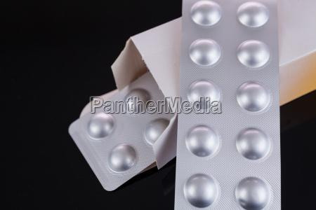 tabletten in silberfolie auf schwarzem hintergrund