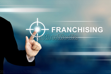 business hand clicking franchising button on