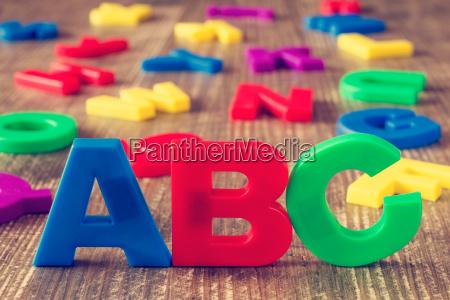 abc schreibweise und stapel von farbbuchstaben