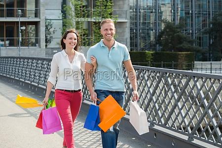 paar walking auf bruecke mit einkaufstaschen