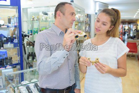 man showing opera glasses to lady