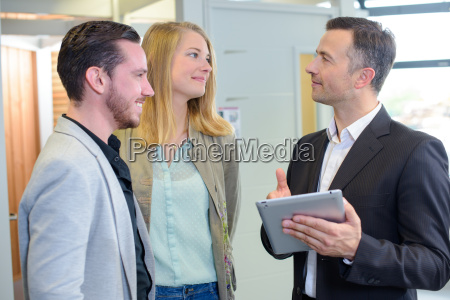 couple with salesman holding tablet