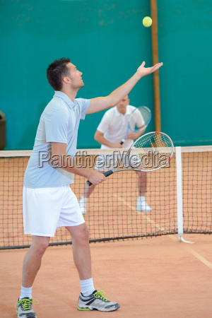 young man doing tennis service