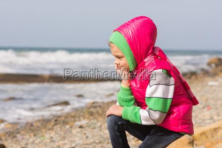 girl sitting on the rocky beach