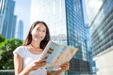 woman using city map and looking