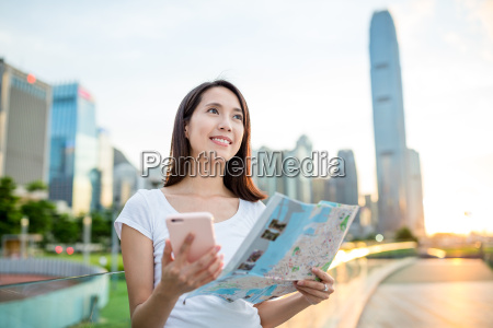woman using cellphone and city map