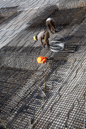 workers construct the iron rods for