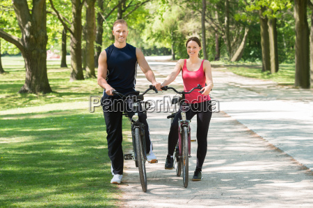 happy couple standing with bicycles