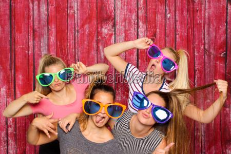 maedchengruppe mit brillen albern vor einer