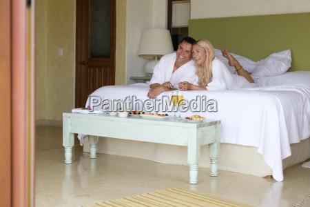 happy couple in bathrobes lying on