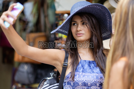 young woman trying a hat on