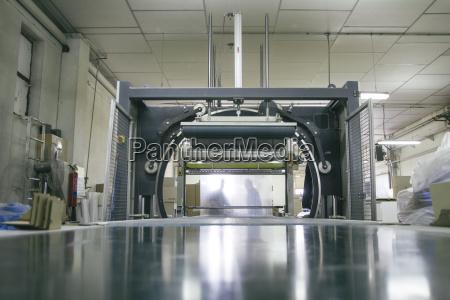 silhouetten von mitarbeitern hinter verpackungsmaschine in