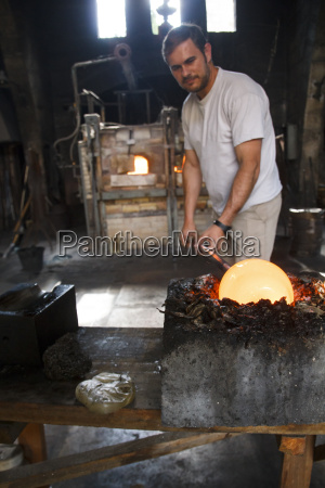 man putting molten glass in a