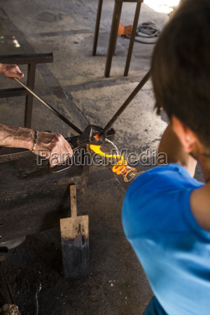 men working with molten glass in
