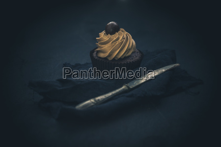 cupcake mit schokoladencreme vor dunklem hintergrund