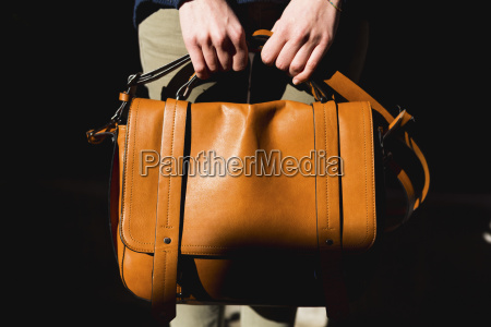 womans hands holding leather bag close