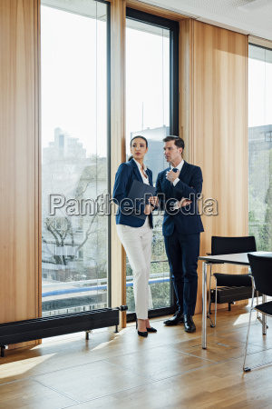businessman and businesswoman in office talking
