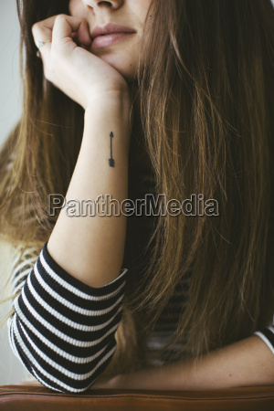 young woman with arrow tatoo on
