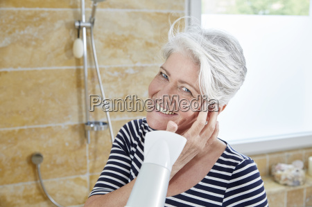 portrait of smiling woman blow drying