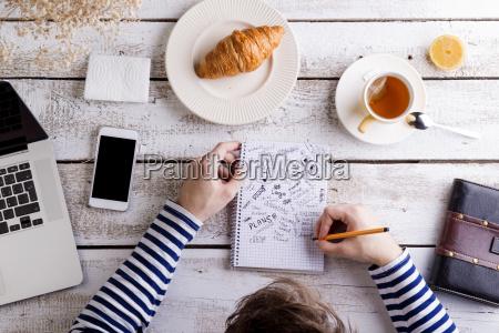 mann arbeitet am tisch mit croissant