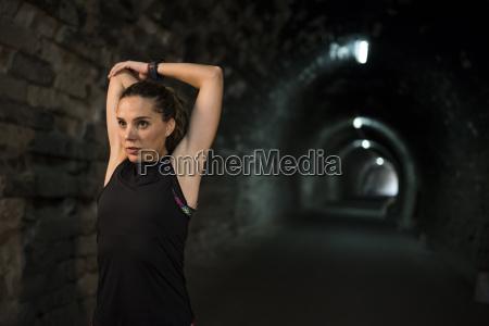 sportive frau in einem tunnel stretching
