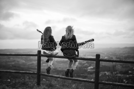 two women sitting on wooden fence