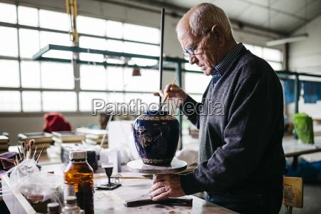 senior mann dekorieren keramikvase in seiner