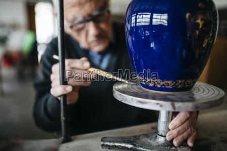 seniorenmensch schmueckt keramikvase in seiner freizeit
