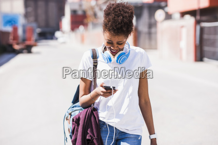 smiling young woman wearing headphones looking
