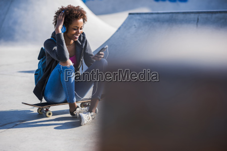 smiling young woman sitting on skateboard