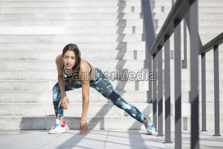 young woman exercising at stairs