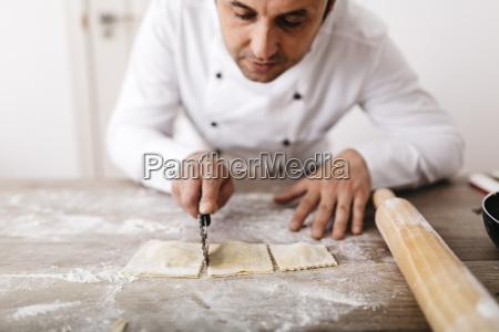 chef schneidet frische ravioli