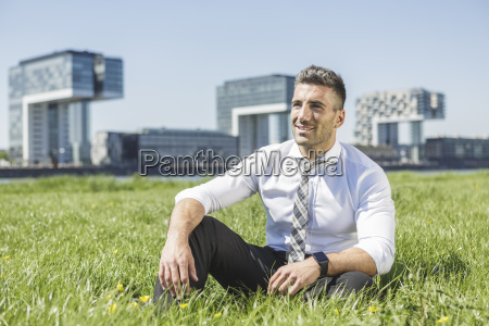 germany cologne smiling businessman sitting in