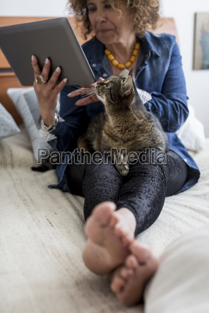 woman with cat on bed holding