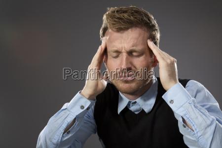 portraet eines mannes der unter kopfschmerzen