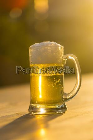 glas frisches bier in der abenddaemmerung