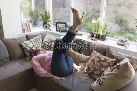 mature man wearing high heels lying