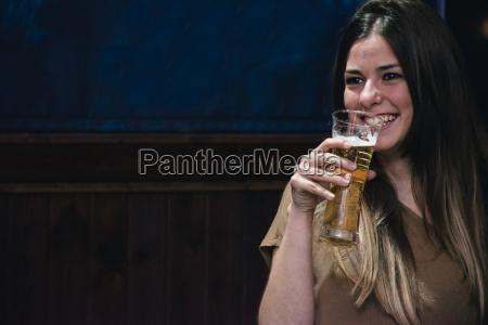 laechelnde frau trinkt ein glas bier
