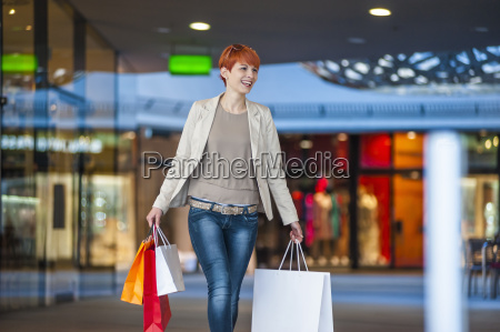 smiling young woman walking with shopping