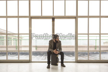 hipster businessman with briefcase waiting in