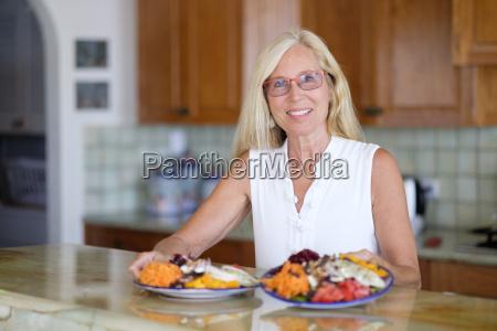 portrait of smiling senior woman serving