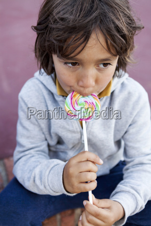 portrait of little boy with lollipop